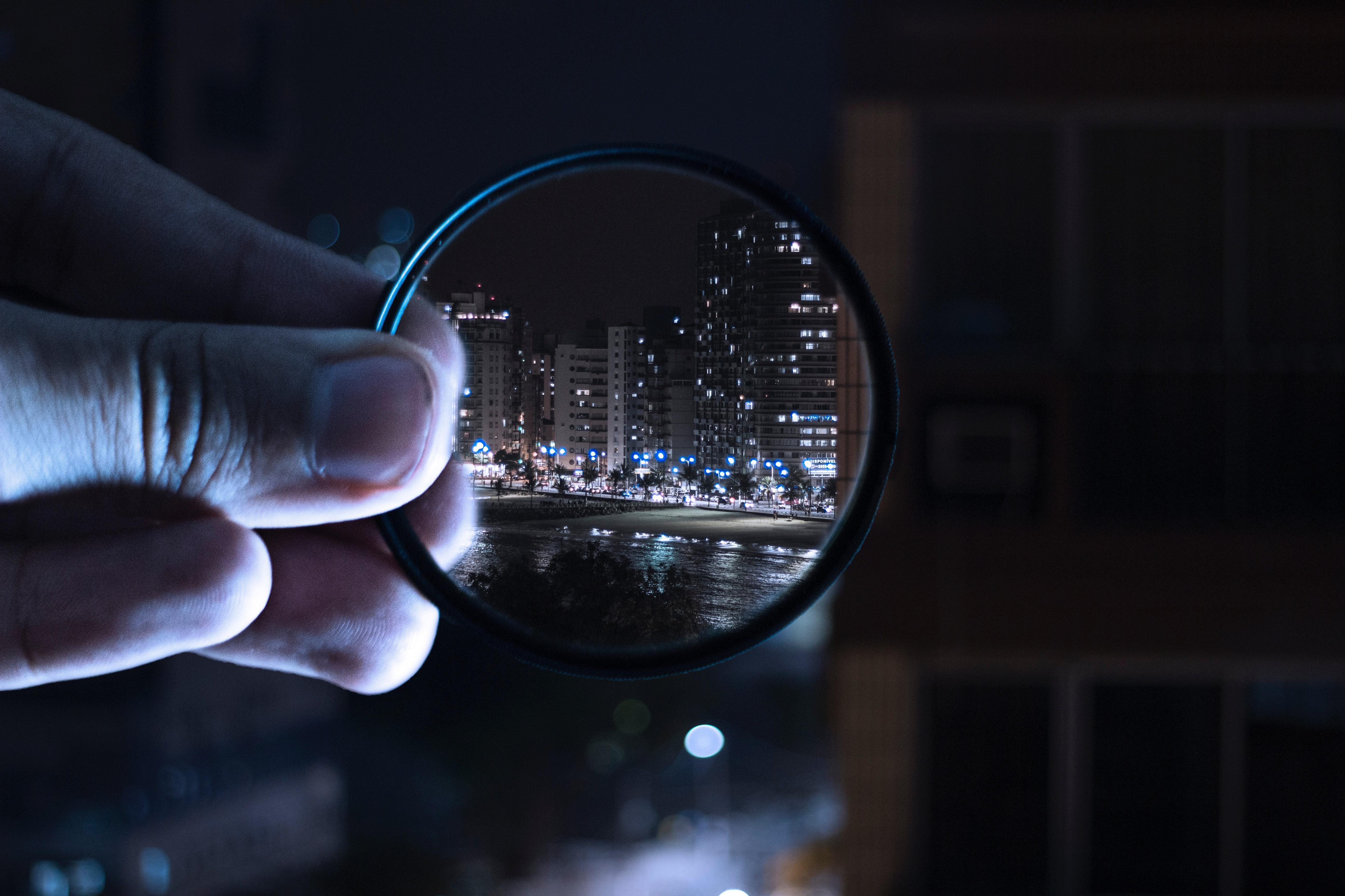 Photo d'une ville vue à travers une loupe illustrant l'importance de l'optimisation de l'investissement local
